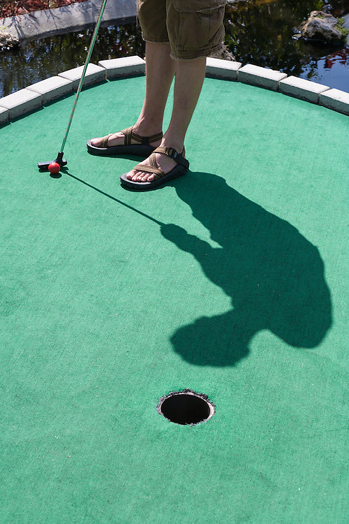 Shadow of mini golf player points to the hole he putts for on green astroturf