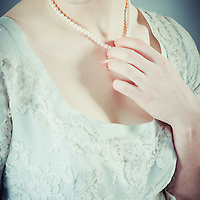 Young woman with short brown hair wearing period lace dress with pearl necklace