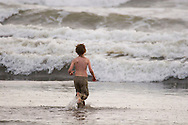 Male child playing in the ocean waves on the coast of Washington at Ocean Shores