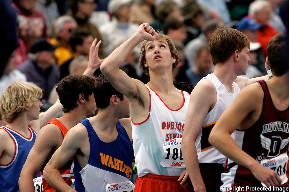 A competitor in a high school relay looks heavenward before his carry at the Drake Relays.  photo by david peterson