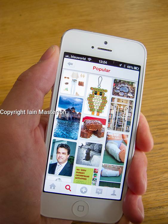 Using Pintrest social media app on  white iPhone 5 smartphone