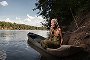 An old woman from Kbal Romeas sitting on a typical wooden canoe in the Srekor river, one of the main tributaries of the Mekong in Stung Treng, northern Cambodia. Most of the people left the village already and the boats are rarely used for fishing; instead old people use them to hang on to while bathing in the river.