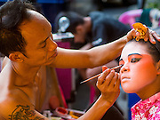 16 JANUARY 2015 - BANGKOK, THAILAND: Performers with Sai Yong Hong Teochew Opera Troupe help each other get ready for a performance at the Chaomae Thapthim Shrine, a Chinese shrine in a working class neighborhood of Bangkok near the Chulalongkorn University campus. They don't have dressing rooms per se, instead setting up their make up tables right on the sidewalk. The troupe's nine night performance at the shrine is an annual tradition and is the start of the Lunar New Year celebrations in the neighborhood. Lunar New Year, also called Chinese New Year, is officially February 19 this year. Teochew opera is a form of Chinese opera that is popular in Thailand and Malaysia.   PHOTO BY JACK KURTZ