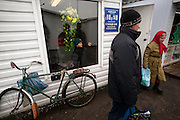 A woman exits a small store selling only dairy products at the main outdoor market in Hoiniki on Oct. 24, 2009.