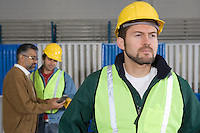 Serious man standing in factory colleagues in background