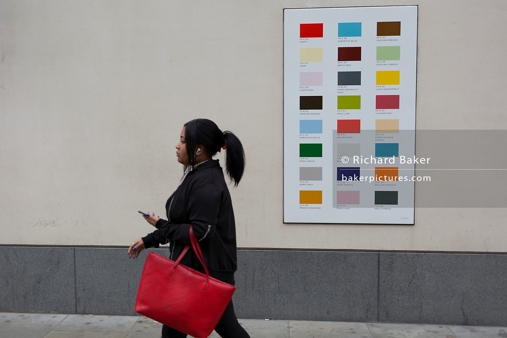 A woman carrying a red bag walks past a colour swatch on the wall of a central London business, on 22nd November 2017, in London England.