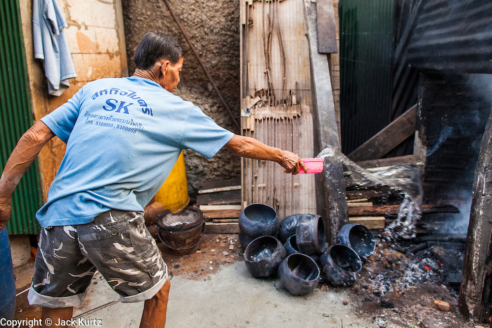 """03 DECEMBER 2012 - BANGKOK, THAILAND:  A bowl maker puts out his kiln after firing monks' bowls, called """"bat"""" (pronounced with a long """"a"""" as in baat) on Soi Baan Bat in Bangkok. The bowls are made from eight separate pieces of metal said to represent the Buddha's Eightfold Path. The Monk's Bowl Village on Soi Ban Baat in Bangkok is the only surviving one of what were originally three artisan's communities established by Thai King Rama I for the purpose of handcrafting """"baat"""" the ceremonial bowls used by monks as they collect their morning alms. Most monks now use cheaper factory made bowls and the old tradition is dying out. Only six or seven families on Soi Ban Baat still make the bowls by hand. Most of the bowls are now sold to tourists who find their way to hidden alleys in old Bangkok. The small family workshops are only a part of the """"Monk's Bowl Village."""" It is also a thriving residential community of narrow alleyways and sidewalks.  PHOTO BY JACK KURTZ"""