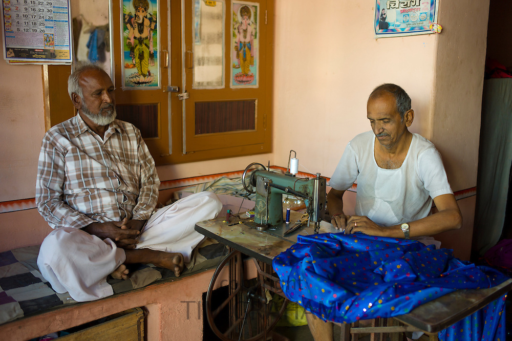 Indian man with old sewing machine making sari in Narlai village in Rajasthan, Northern India