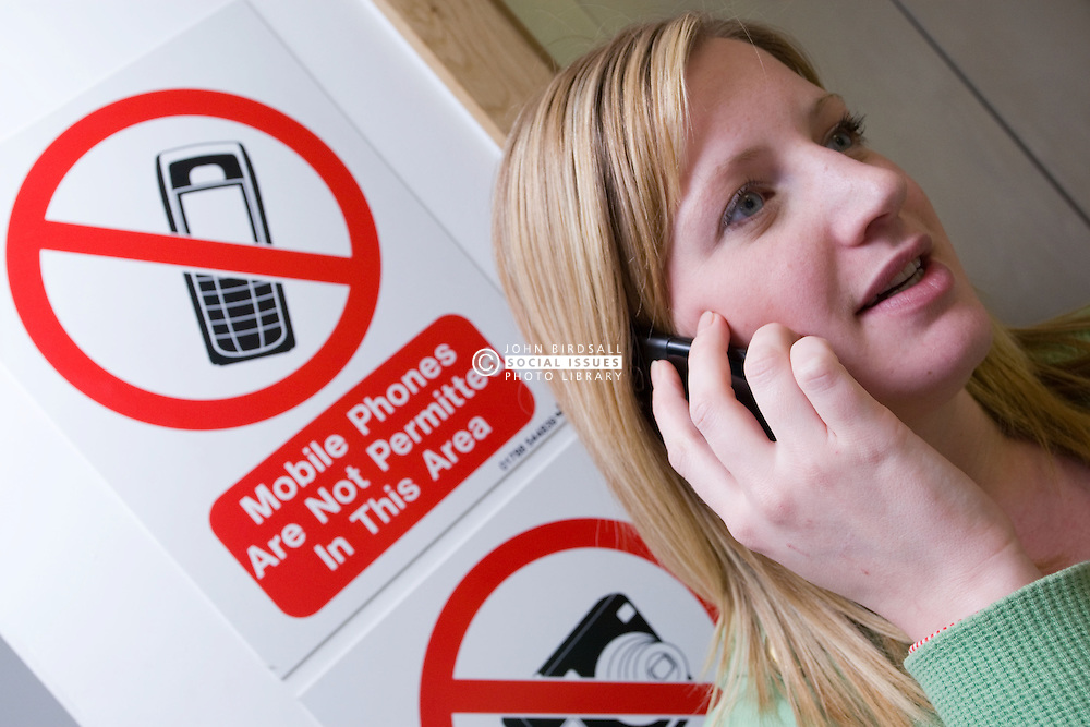 Young woman making a phone call whilst ignoring the sign in the background prohibiting the use of mobile phones in the area,