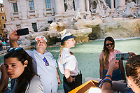 """ROME, ITALY - 20 JUNE 2017: A Roman policewoman, entrusted to protect the Fountain of Trevi, is seen here with tourists by the fountain in Rome, Italy, on June 20th 2017.<br /> <br /> The warm weather has brought a menacing whiff of tourists behaving badly in Rome. On April 12, a man went skinny-dipping in the Trevi fountain resulting in a viral web video and a 500 euro fine.<br /> <br /> Virginia Raggi, the mayor of Rome and a national figurehead of the anti-establishment Five Star Movement,  issued an ordinance involving harsher fines for eating, drinking or sitting on the fountains, for washing animals or clothes in the fountain water or for throwing anything other than coins into the water of the Trevi Fountain, Bernini's Four Fountains and 35 other city fountains of artistic or historic significance around the city.  """"It is unacceptable that someone use them to go swimming or clean themselves, it's an historic patrimony that we must safeguard,"""" Ms. Raggi said."""