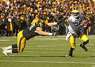 November 23 2013: Michigan Wolverines quarterback Devin Gardner (98) scrambles away from Iowa Hawkeyes defensive lineman Mike Hardy (98) during the second quarter of the NCAA football game between the Michigan Wolverines and the Iowa Hawkeyes at Kinnick Stadium in Iowa City, Iowa on November 23, 2013. Iowa defeated Michigan 24-21.