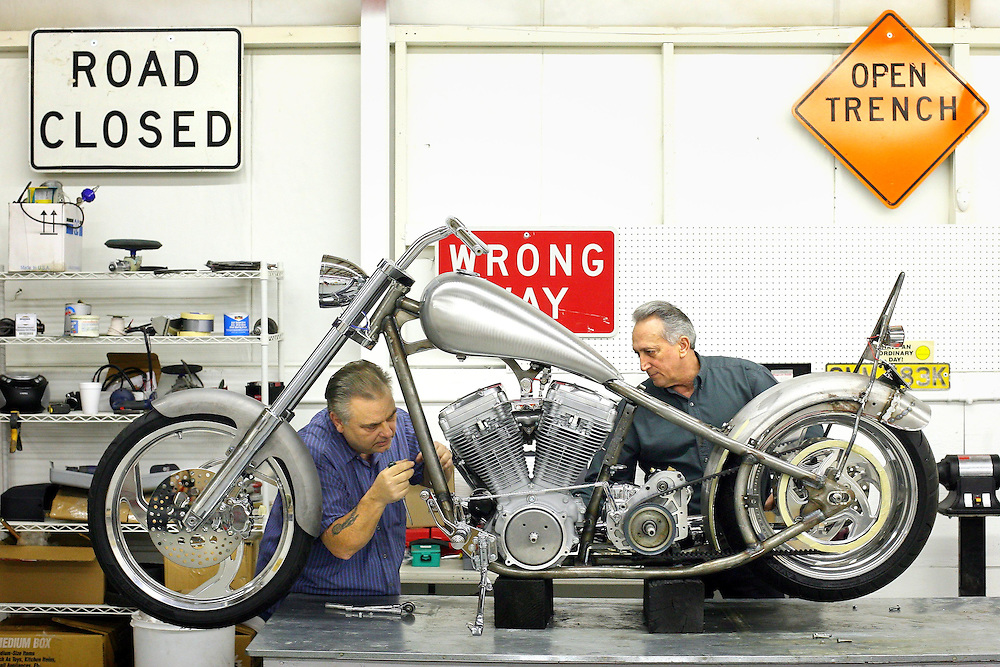 JEROME A. POLLOS/Press..Sonny Maxwell, left, and A.J. Basile, owner of Classic Rides & Customs Inc., disassemble their first 2006 Renegade Outlaw that will tour the west coast to promote motorcycle's manufacturing business Coeur d'Alene under Basile's ownership. Basile, purchased the manufacturing license of the Las Vegas company this year, and will build the Harley-powered cruisers at his sales office at 1705 Northwest Blvd.
