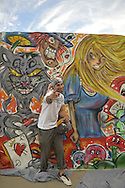 JEAN PAUL SALIBA, aka Draft, of Farmingdale, is a graffiti artist creating an outdoor mural of Alice in Wonderland characters, at the United Ink Flight 914 tattoo convention at the Cradle of Aviation museum of Long Island.