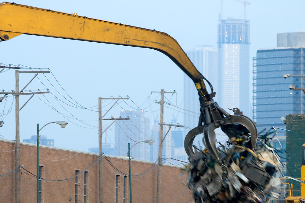 A magnetic claw swings a load of scrap metal into a pile at a junk yard on the north side of Chicago, IL.