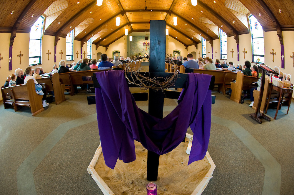 A small cross draped with a purple cloth and displaying a crown of thorns is erected at the entrance of St. Philip Church in Green Bay during Holy Week. (Sam Lucero photo)