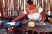 MEXICO, YUCATAN, MAYAN mother cooking tortillas in palapa