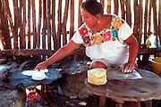 MEXICO, YUCATAN, MAYAN mother cooking tortillas in palapa