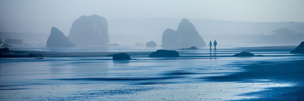 A couple explores the beach at dawn in Bandon , Oregon