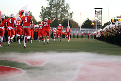 25 October 2014: The man made fog lingers and billows just above the turf as the Redbirds storm the field between rows of the Beg Red Marching Machine during an NCAA Missouri Valley Conference game between the Missouri State Bears and the Illinois State Redbirds at Hancock Stadium in Normal, Illinois.