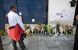 © Licensed to London News Pictures. 20/06/2017. London, UK. A postman looks at floral tributes and candles are left in Whadcoat Street in Finsbury Park in north London where a van ploughed into a crowd near Finsbury Park Mosque.  One person has been killed and 10 people are injured. Darren Osborne, 47, from Cardiff, continues to be held on suspicion of attempted murder and alleged terror offences.  Photo credit: Peter Macdiarmid/LNP