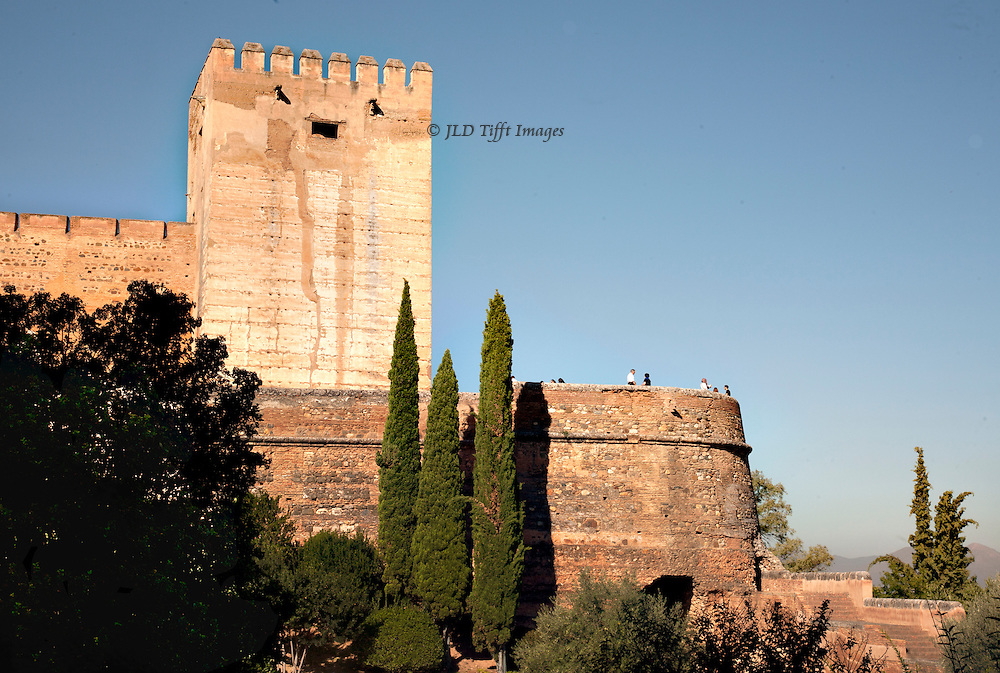 The Alhambra as fortress, seen from the Albaicin section of Grenada.  Powerful walls, square tower, and a scattering of tourists along the wall. Three cypresses and a cluster of other greenery in the foreground.