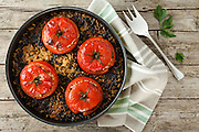 Baked tomatoes stuffed with rice and chard on wood table, overhead shot.