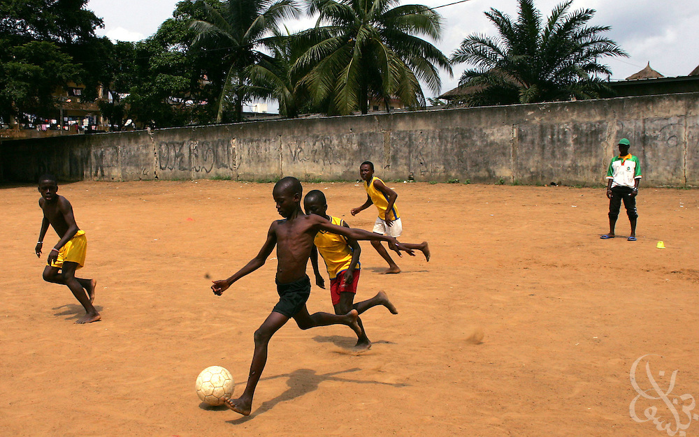 Barefoot Ivorian boys play an afternoon practice game at the Olympic Sport Abobo club in the Abobo neighborhood of Abidjan, Ivory Coast February 18, 2006. Spawned from the success of the ASEC academy, some 300 rival football academies have arisen in Abidjan, mostly in poorer neighborhoods, and looking to reproduce the same results on the cheap, with little or no emphasis placed on education.