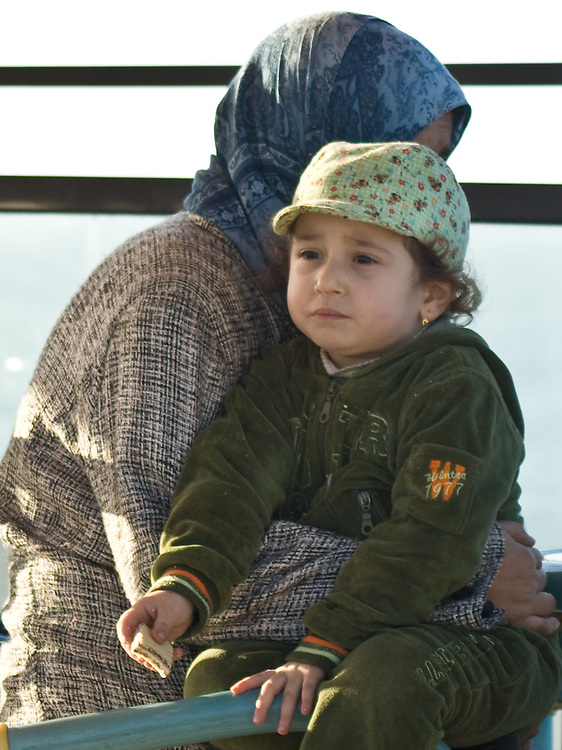 Young girl sits in her mother's lap overlooking the Atlantic Ocean in Casablanca.
