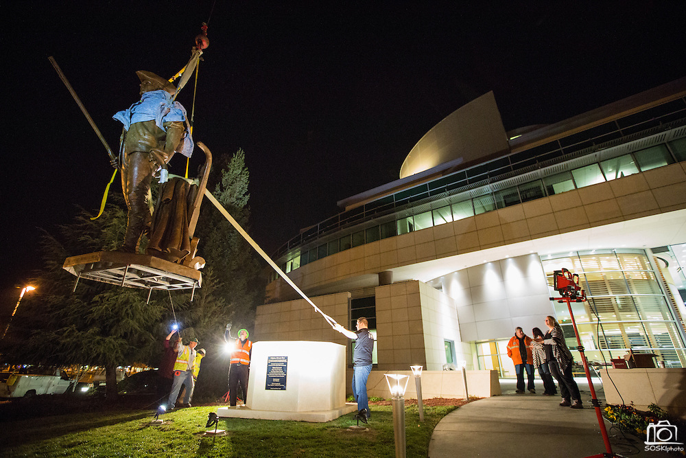 Workers guide the 12-foot Milpitas Minute Man sculpture into place with a crane, outside Milpitas City Hall in Milpitas, California, on January 24, 2014.  The sculpture was created by David Alan Clark, took 10 months to complete, and weighs approximately 2,500 pounds. (Stan Olszewski/SOSKIphoto)