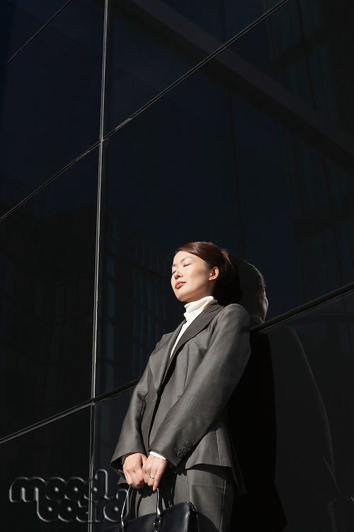 Businesswoman Leaning eyes closed Against Wall outside