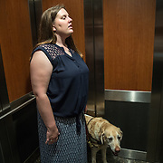 ARLINGTON, VA -JUNE3:  Tiffany Jolliff with her assistance dog, Railey, in the elevator of her apartment building in Arlington, VA, June 3, 2016. The Washington Lawyers' Committee for Civil Rights and Urban Affairs filed a lawsuit Thursday in federal district court in the Eastern District of Virginia on behalf of Tiffany Jolliff against Uber, alleging violations of the Americans With Disabilities Act and the Virginians with Disabilities Act, alleging Uber unlawfully refused to accommodate Jolliff, who is blind, and her service dog, Railey. The complaint alleges that Jolliff, who works as a policy specialist for the federal government on employment for workers with disabilities, has been repeatedly discriminated against and denied Uber's services when Uber's drivers have seen that she is accompanied by her service dog Railey. Specifically, instead of accommodating her service dog Railey, as both the ADA and VDA require, Uber drivers have repeatedly driven off upon seeing that Ms. Jolliff had a service dog. (Photo by Evelyn Hockstein/For The Washington Post)