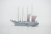 Four-masted schooner hoisting sails in the fog, Bar Harbor, Maine