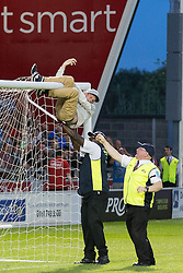 Image ©Licensed to i-Images Picture Agency. 07/08/2014. Salford, United Kingdom. Class of 92 Manchester. AJ Bell Stadium. Pitch invader swinging from goal . Class of 92 squad play Salford City FC at the AJ Bell Stadium . Picture by i-Images