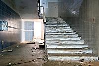 """La rampa di scale che collega il piano terra e il primo piano dell'ex centro di permanenza temporanea """"Casa Regina Pacis"""" a San foca (LE) ormai in disuso. 21/02/2010 (PH Gabriele Spedicato)..I Centri di permanenza temporanea (CPT), ora denominati Centri di identificazione ed espulsione (CIE), sono strutture istituite in ottemperanza a quanto disposto all'articolo 12 della legge Turco-Napolitano (L. 40/1998) per ospitare gli stranieri """"sottoposti a provvedimenti di espulsione e o di respingimento con accompagnamento coattivo alla frontiera"""" nel caso in cui il provvedimento non sia immediatamenti eseguibile."""