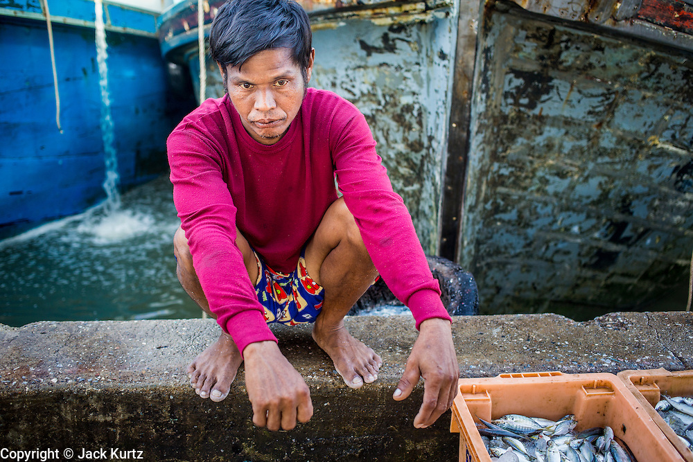 30 OCTOBER 2012 - PATTANI, PATTANI, THAILAND:  A Burmese man who crews a Thai fishing trawler relaxes in the port of Pattani, province of Pattani, Thailand. Thailand's fishing industry relies on immigrant workers, mostly from Myanmar but also Laos and Cambodia. There have been allegations of worker abuse, including charges that workers are held in slave labor like conditions.  There are hundreds of thousands of immigrant workers in the Thai fishing industry. Most are from Myanmar (Burma) but there are also Cambodian and Laotian workers in the industry.    PHOTO BY JACK KURTZ