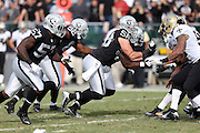 Oakland Raiders defensive end Dave Tollefson (58) and a group of defensive players rush the quarterback at the line of scrimmage during the NFL week 11 football game against the New Orleans Saints on Sunday, Nov. 18, 2012 in Oakland, Calif. The Saints won the game 38-17. ©Paul Anthony Spinelli