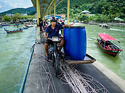 23 AUGUST 2018 - TELUK BAHANG, PENANG, MALAYSIA: A motorcycle hauls supplies out to commercial fishing trawlers in port in Teluk Bahang on the island of Penang. Fishermen on Penang, an island off the west coast of mainland Malaysia, are being pressured by the island's resort development and reduce catches in the waters off Malaysia.     PHOTO BY JACK KURTZ