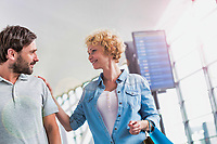 Portrait of mature couple walking while talking in airport