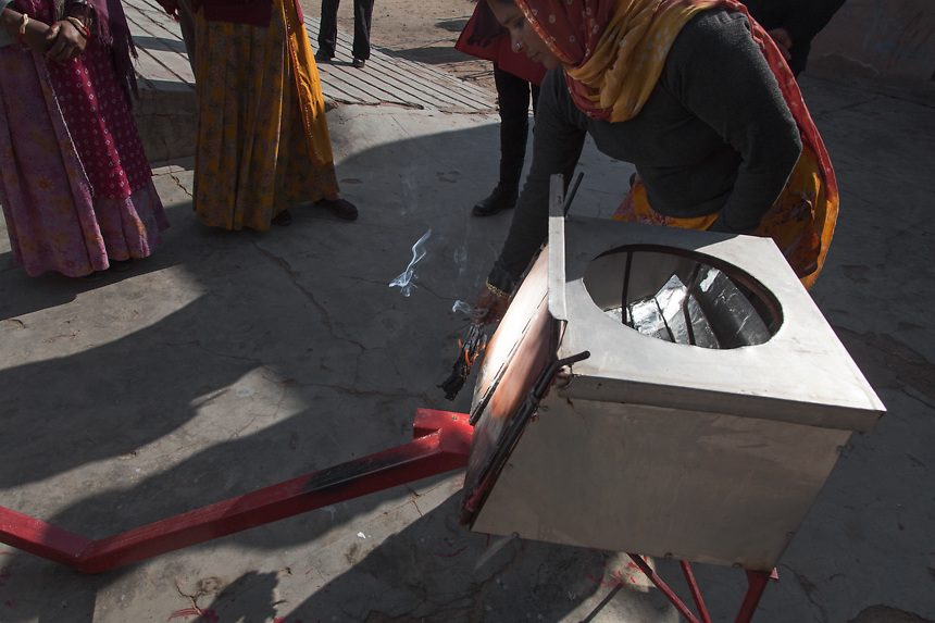 A woman burning a peace of paper, to show how is working a parabolic solar cooker, that uses sunlight energy to cook food. Its shape and construction allows the sun's rays to fall on 300 mirrors that in turn reflect them onto the bottom of a cooking pot. 01/2013 © Marida Augusto/Max Hirzel