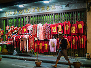 """08 FEBRUARY 2016 - BANGKOK, THAILAND:  A man walks past a sidewalk stand selling Chinese New Year's clothes in Bangkok's Chinatown district during the celebration of the Lunar New Year. Chinese New Year is also called Lunar New Year or Tet (in Vietnamese communities). This year is the """"Year of the Monkey."""" Thailand has the largest overseas Chinese population in the world; about 14 percent of Thais are of Chinese ancestry and some Chinese holidays, especially Chinese New Year, are widely celebrated in Thailand.      PHOTO BY JACK KURTZ"""