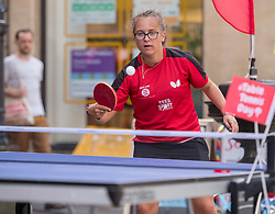 © Licensed to London News Pictures. 18/07/2019; Bristol, UK. National Table Tennis Day in the UK. MARIA TSAPSINOS, National Singles Champion and Bronze medallist in the 2018 Commonwealth Games, plays with members of the public in Corn Street in the city centre and with Junior England International Louis Price in the Ping Pong Parlour in the Galleries Shopping Centre. Photo credit: Simon Chapman/LNP.