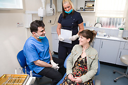 Dentist; with assistance of dental nurse;  in consultation with patient,