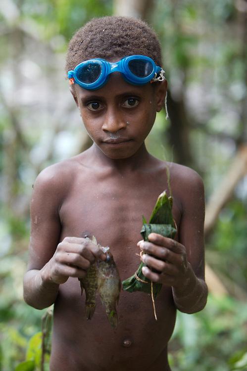 A young korowai boy after a succesful fishing trip.
