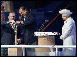 Image licensed to i-Images Picture Agency. 23/07/2014. Glasgow, United Kingdom. The Queen watches as Commonwealth Games Federation President  Prince Imran struggles to take The Queen's message from the baton along with Sir Chris Hoy  at the Commonwealth Games opening ceremony in  Glasgow. Picture by Stephen Lock / i-Images