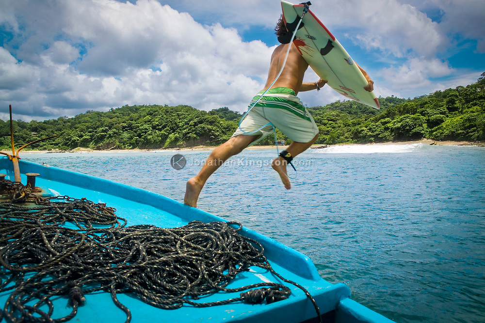 A surfer jumps off the boat to swim toward the break and catch a wave in to Maderas Beach, located near San Juan Del Sur, Nicaragua. Once a little known and sleepy vacation spot, San Juan Del Sur has become increasingly popular for its beautiful beaches, small fishing town feel, and respected surf break.