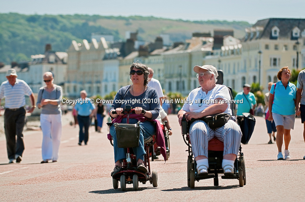 Female wheelchair and mobility scooter users on promenade<br /> Llandudno<br /> Conwy County<br /> North<br /> Towns and Villages