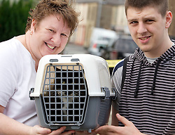 © Licensed to London News Pictures. 27/06/2012. Oldham , UK . A large explosion , believed to be caused by gas , has brought down at least one house in an Oldham terrace . Felix the cat is rescued from 4 Gordon Street by a member of fire services crew to the delight of his owners . Left to right - Julie Wilts , Felix the cat , and Julie's son , Jack Wilts . Photo credit : Joel Goodman/LNP