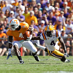 Oct 2, 2010; Baton Rouge, LA, USA; Tennessee Volunteers wide receiver Gerald Jones (4) escapes a tackle by LSU Tigers cornerback Jai Eugene (4) during the first half at Tiger Stadium.  Mandatory Credit: Derick E. Hingle