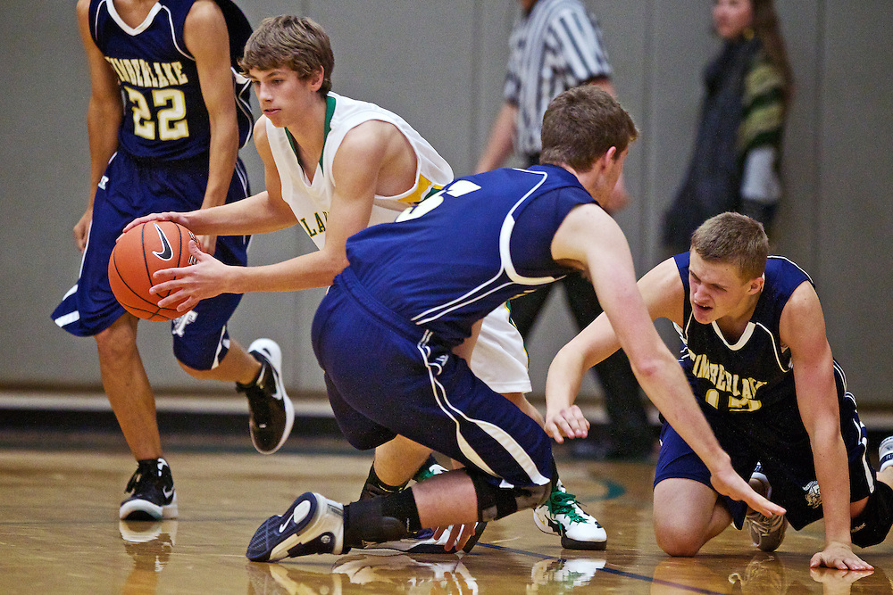 Lakeland High's Tyrel Derrick escapes with the ball after wrestling it away from Trevor Masterson, right, and Brian Cronnelly from Timberlake High during the YEA boys basketball jamboree Monday at Lake City High.