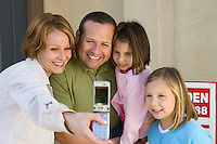 Family with two children (6-9) photographing with mobile